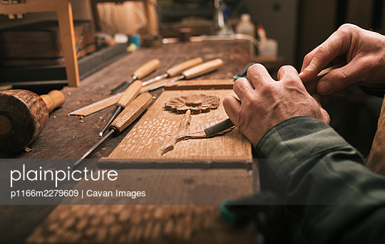 Close up of cabinetmaker working on a wood carving with a chisel. - p1166m2279609 by Cavan Images