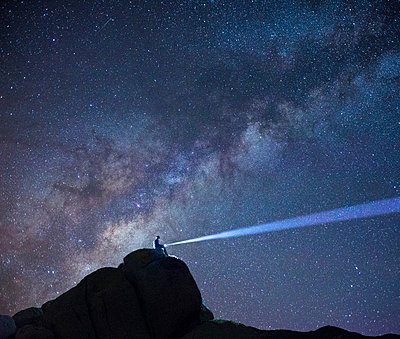 Silhouette hiker with flashlight sitting on mountain against star field at Joshua Tree National Park - p1166m1526591 by Cavan Images