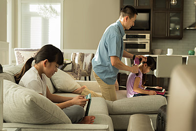 Girl using digital tablet while father combing her daughters hair at home - p1315m1565965 by Wavebreak