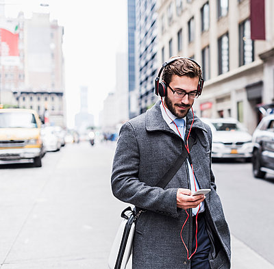 USA, New York City, businessman with cell phone and headphones on the go - p300m1192263 by Uwe Umstätter