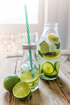 Glass bottles of infused water with lemon, lime, mint leaves and ice cubes - p300m1356108 by Giorgio Fochesato