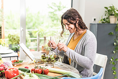 Woman making salad while using digital tablet at home - p300m2227215 by Uwe Umstätter