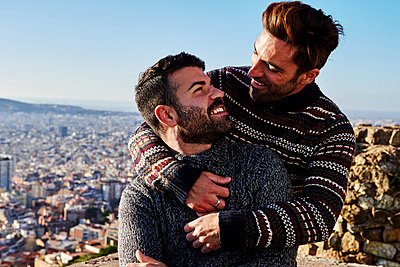 Romantic gay men looking at each other against clear sky, Bunkers del Carmel, Barcelona, Spain - p300m2257323 by Veam