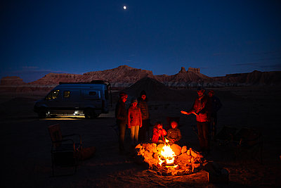 Family at night-time campfire in the desert, Utah, USA - p756m2263762 by Bénédicte Lassalle