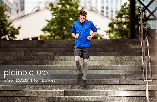 Young runner jogging down steps, London, UK - p429m2075351 by Tom Dunkley