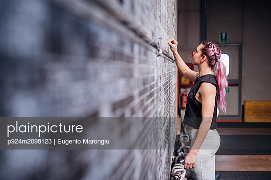 Young woman writing on scoreboard in gym - p924m2098123 by Eugenio Marongiu