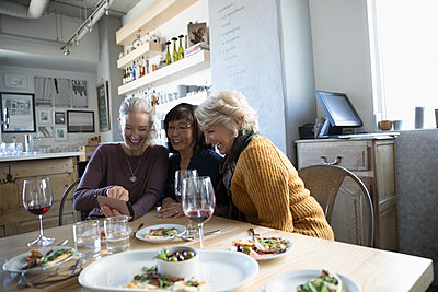 Active senior women friends with camera phone enjoying appetizers and red wine in cafe - p1192m1567179 by Hero Images
