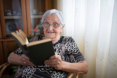 Senior woman reading a book at home - p300m1059163f by Ramon Espelt