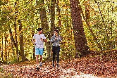 Couple jogging on autumnally forest track - p300m1581341 von Stefan Hobmaier