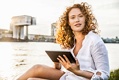 Germany, Cologne, portrait of young woman with tablet sitting at riverside - p300m2029214 by Jo Kirchherr