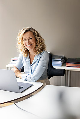 Smiling female business professional with laptop sitting at desk in office - p300m2267115 by Peter Scholl