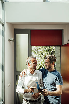 Father and son standing near entrance at home - p300m2275037 by Gustafsson