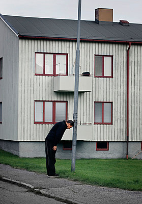 Man leaning at lamp post - p312m714745 by Bruno Ehrs