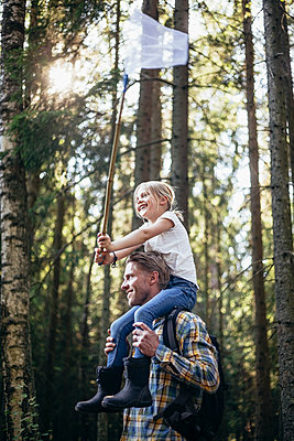 Low angle view of smiling father carrying daughter on shoulder with fishing net in forest - p426m2213192 by Maskot