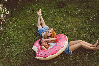 Freundinnen entspannen mit Donut Schwimmreifen im Garten - p432m2260295 von mia takahara