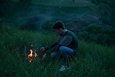 Caucasian man starting campfire at night - p555m1504178 by Dmitriy Bilous