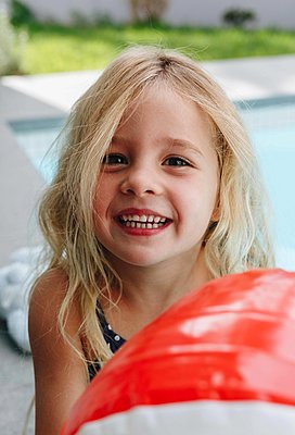Happy little girl with ball sitting by swimming pool - p924m2138323 by Image Source