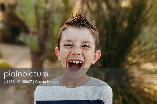 Close up portrait of cute young boy with freckles laughing outdoors - p1166m2136647 by Cavan Images