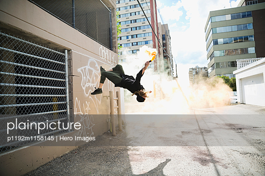 Cool young man doing parkour backflipping with powder cannon in urban alley