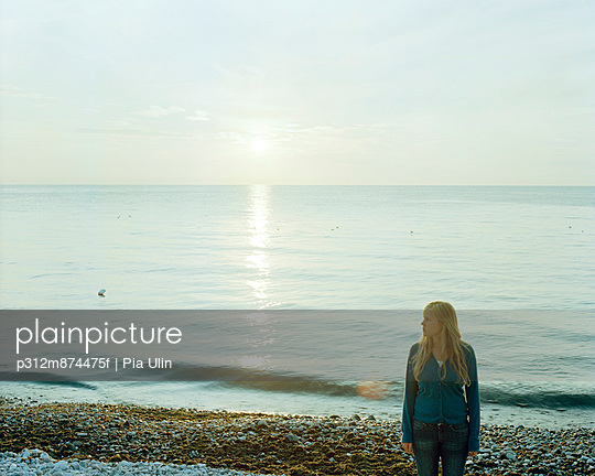 Girl standing on beach - p312m874475f by Pia Ulin