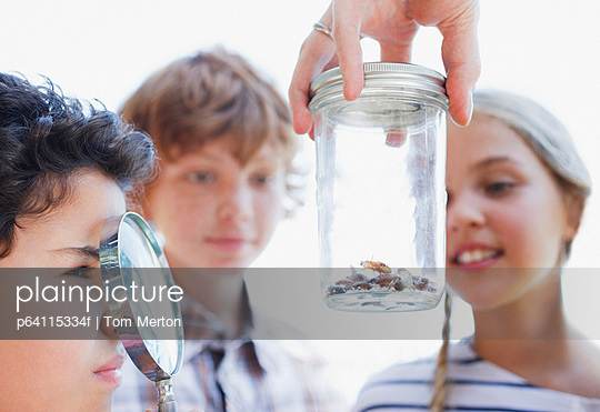 Kids looking at insects in jar with magnifying glass