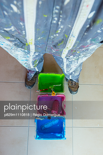 Person in protective clothing with paint buckets - p829m1110818 by Régis Domergue