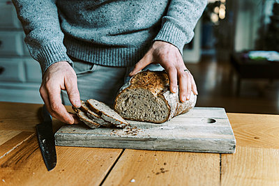 Hands of a man holding and cutting a rustic sourdough bread with knife - p1166m2236612 by Cavan Images
