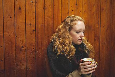 Woman holding a coffee mug in cafe - p1315m2062641 by Wavebreak