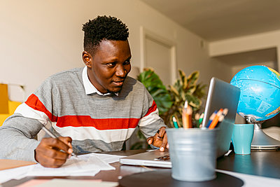 Smiling male entrepreneur looking at laptop while writing on paper in home office - p300m2241178 by Valentina Barreto