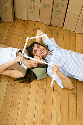 Young couple lying on wooden floor - p6090290f by DRESDEN photography