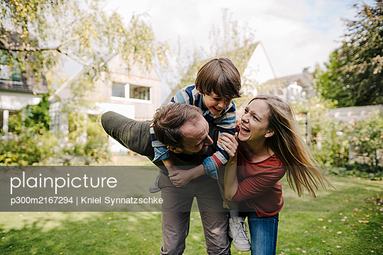 Parents and son having fun, playing in the garden - p300m2167294 by Kniel Synnatzschke