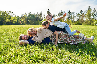 Happy family enjoying while lying on grass during sunny day - p300m2197366 by Stefanie Aumiller