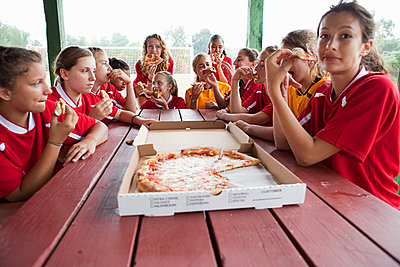 Female soccer team having pizza - p9245352f by Image Source