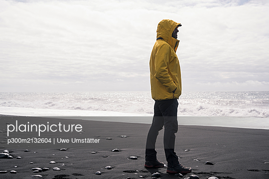 Mature man on a lava beach in Iceland, looking at the sea - p300m2132604 by Uwe Umstätter