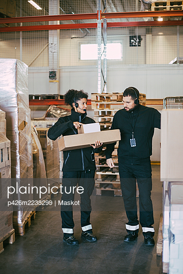 Female entrepreneur holding packages while discussing with male colleague in logistics warehouse - p426m2238299 by Maskot