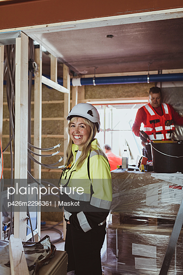 Happy female building contractor standing with hand in pocket while male construction worker working at site - p426m2296361 by Maskot