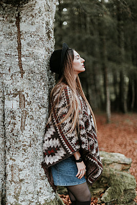Young woman wearing hat and poncho leaning against tree trunk in autumnal forest - p300m1549416 by Oriol Castelló Arroyo