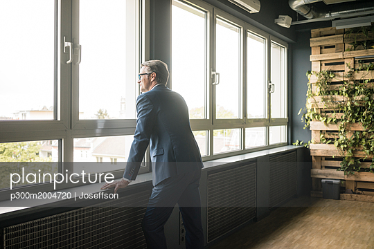 Mature businessman standing at the window in office - p300m2004720 von Joseffson