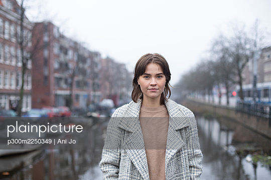 Female in warm clothing standing by canal against sky - p300m2250349 by Ani Jo