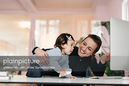 Junge Geschäftsfrau mit Tochter im Büro - p586m1451944 von Kniel Synnatzschke