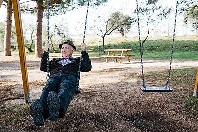 Spain, Barcelona. Retired senior man swinging on a children's park swing - p300m2167190 von Josep Rovirosa