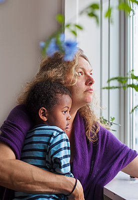 Mother with son looking through window - p312m2237218 by Pernille Tofte