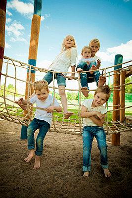 Full length of five children playing on rope bridge in garden - p426m719525f by Katja Kircher