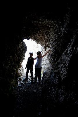 Little siblings exploring cave - p426m719744f by Katja Kircher