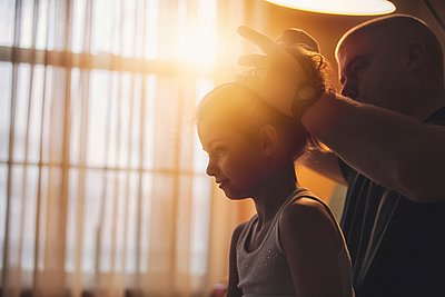 Father doing his daughter's hair - p429m1105699 by Rebecca Nelson