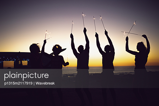 Friends playing with sparklers on the beach at dusk - p1315m2117919 by Wavebreak