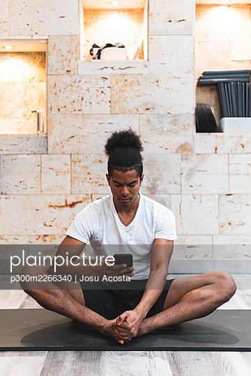 Man using smart phone while exercising Pilates at yoga studio - p300m2266340 by Josu Acosta
