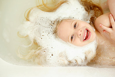 Overhead view of cheerful girl bathing in bathtub - p1166m1174053 by Cavan Images