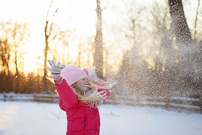Girl in warm clothing throwing snow while standing against sky - p1166m1174060 by Cavan Images