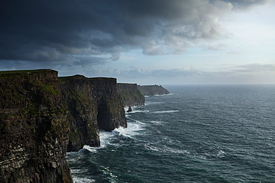 Scenic view of cliffs and sea against cloudy sky - p1166m1174295 by Cavan Images